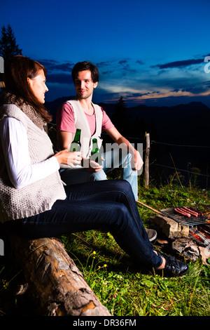 Tirol - junge Paar auf Almwiese eines Berges am Lagerfeuer in den Bayerischen Alpen sitzen und genießt den romantischen - Stockfoto