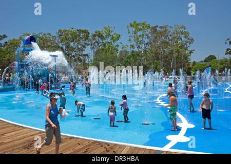 Masse der Erwachsenen & Kinder zu Fuß durch Wasser & immer unter Wasser durchnäßt kippte aus riesigen Eimer in Hervey - Stockfoto