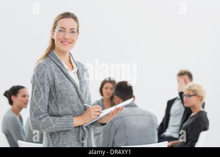 Porträt des Therapeuten mit Gruppentherapie in der Sitzung im Hintergrund - Stockfoto