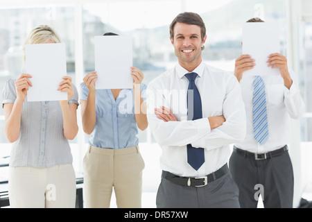 Geschäftsmann mit Kollegen halten Blankopapier vor Gesichtern - Stockfoto