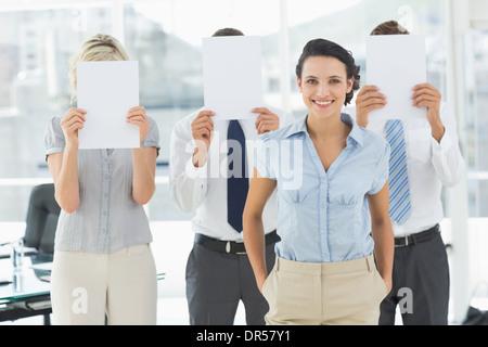 Geschäftsfrau mit Kollegen halten Blankopapier vor Gesichtern - Stockfoto