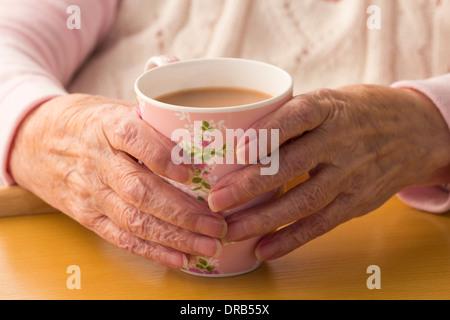Ältere Dame in ihre neunziger Jahre halten Tasse Tee - Stockfoto
