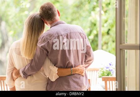 Älteres paar umarmt in Tür - Stockfoto