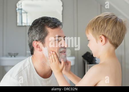 Junge Rasierschaum auf Vaters Gesicht reiben - Stockfoto
