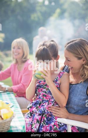 Mädchen trinken Saft auf Mutters Schoß im Hinterhof - Stockfoto