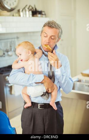 Vater Holding Baby und frühstücken - Stockfoto