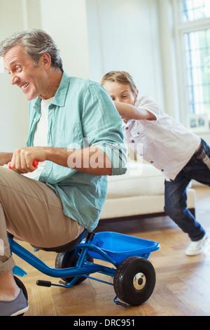 Junge Vater auf Dreirad drinnen drängen - Stockfoto