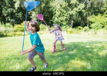 Jungen und Mädchen mit Schmetterling Netze Gras laufen - Stockfoto