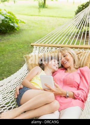 Großmutter und Enkelin mit digital-Tablette in Hängematte - Stockfoto