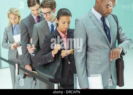 Geschäftsleute, die Überprüfung von Armbanduhren im Wartebereich - Stockfoto
