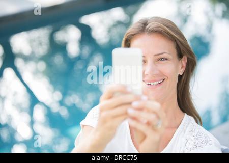 Frau mit Handy am Pool - Stockfoto