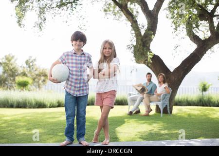 Bruder und Schwester mit Volleyball im Hinterhof - Stockfoto