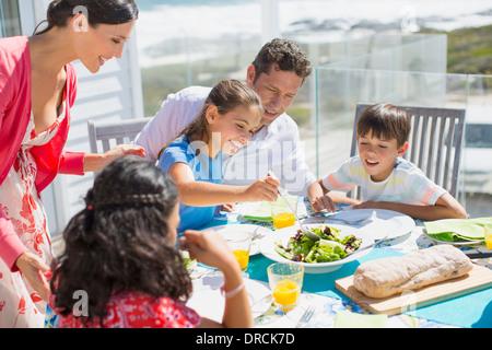 Familie beim Mittagessen am Tisch auf der sonnigen Terrasse - Stockfoto