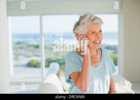 Ältere Frau am Handy im sonnigen Wohnzimmer - Stockfoto