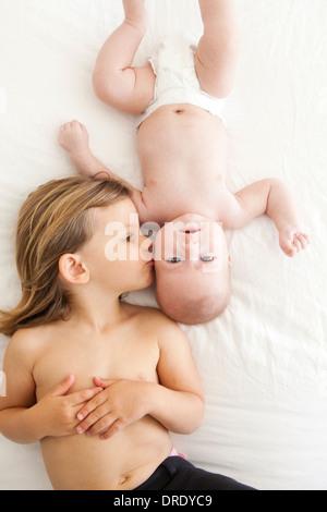 Schwester küssen ihre jüngeren Geschwister - Stockfoto
