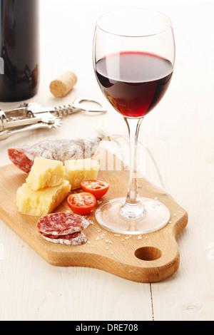 Rotwein und Auswahl an Käse und Snacks auf weißem Hintergrund - Stockfoto