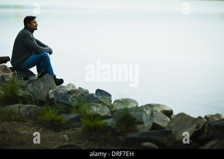 Colorado USA Mann mittleren Alters sitzen auf Felsen suchen nachdenklich - Stockfoto