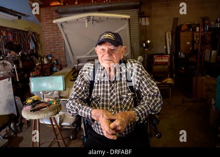 Ein 93-jähriger Mann in seiner Garage, wo er auf Autos arbeitet. - Stockfoto