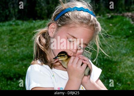 Junges Mädchen küsst ihr Ostern Entlein sanft auf der Rückseite des Halses - Stockfoto