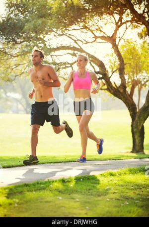 Paar Joggen laufen draußen im Park bei Sonnenaufgang auf schöner Steig. Gesunde Lebensweise Fitnesskonzept. - Stockfoto