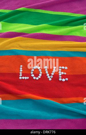 """Das Wort """"Love"""" von Muscheln auf einem bunten Badetuch liegend gebildet - Stockfoto"""