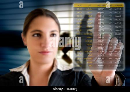 Wählen ihren Flug am Flughafen in eine futuristische Digitalanzeige Geschäftsfrau - Stockfoto