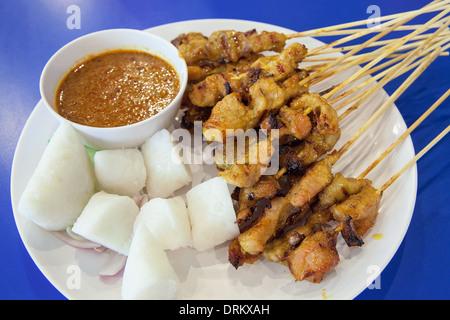 Schweinefleisch-Satay mit Penut Sauce Reis Kuchen Ketupat Zwiebeln und Gurken Closeup - Stockfoto