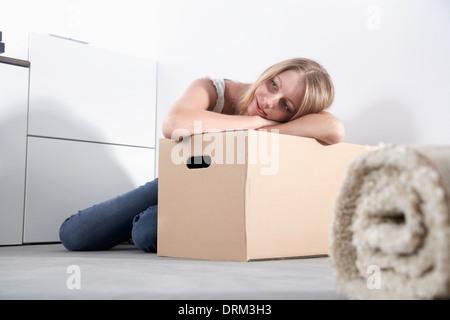 Junge Frau lehnt sich auf Karton - Stockfoto