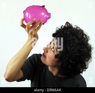 Junge Frau prüft leeren Sparschwein - Stockfoto