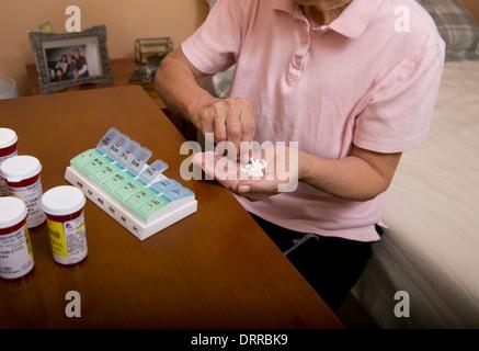 75 Jahre Hispanic Senioren alte organisiert ihr mehrere verschreibungspflichtige Medikamente Pillen in einer wöchentlichen - Stockfoto