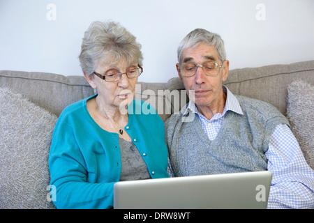 Älteres Paar mit einem Laptop-Computer zu Hause. - Stockfoto