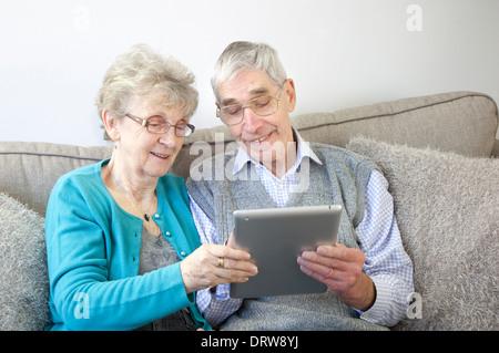 Gerne älteres Paar genießen mit einem digitalen Tablet zu Hause. - Stockfoto