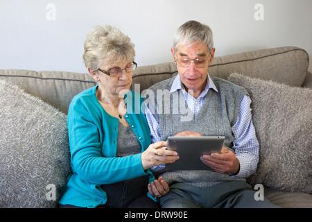 Älteres paar-Sitzung mit einem digitalen Tablet zu Hause. - Stockfoto