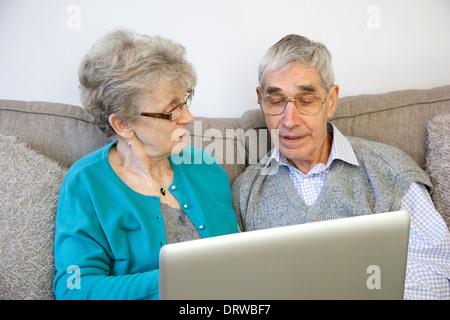Älteres paar-Sitzung mit einem Laptop zu Hause. - Stockfoto