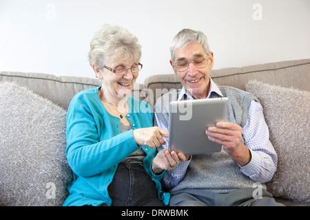 Älteres Paar genießen mit einem digitalen Tablet zu Hause. - Stockfoto