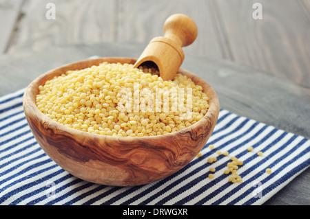 Rohen Couscous in Holzschale auf hölzernen Hintergrund closeup - Stockfoto