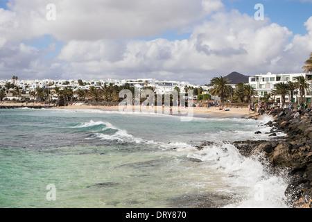 Blick entlang der felsigen Küste zu Sandstrand Playa de Las Cucharas Strand in Costa Teguise, Lanzarote, Kanarische - Stockfoto