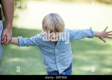 Jungen spielen im Freien, halten die Hand des Vaters - Stockfoto
