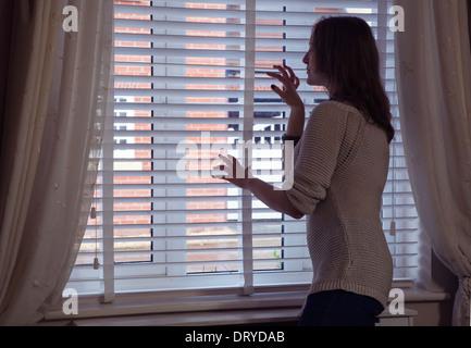 Attraktive junge Frau, Blick durch ein Fenster, hinten/Seitenansicht. - Stockfoto