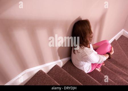 Frau sitzt auf der Treppe zurück Blick.