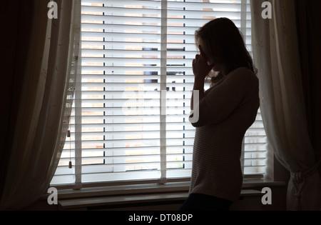 Silhouette der Frau mit dem Kopf in Händen von einem Fenster stehen. Über Schulter Rücken/Seitenansicht. - Stockfoto