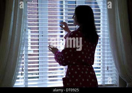 Silhouette der Trägerin einen Morgenmantel aus dem Fenster schauen. Über Schulter Rücken/Seitenansicht. - Stockfoto