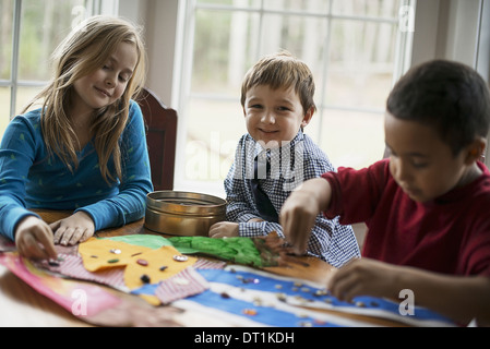 Kinder in einer Familie zu Hause drei Kinder erstellen Bilder mit Leim und Aufkleber Kunsthandwerk - Stockfoto