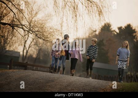 Eine Gruppe von Kindern ein Junge und vier Mädchen zu Fuß entlang eines Pfads an einem Wintertag einen Bio-Bauernhof - Stockfoto
