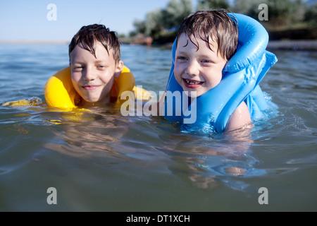 Lächelnde Brüder in die Schwimmweste schwimmen - Stockfoto