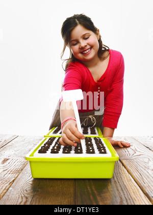 Ein junges Mädchen Pflanzen Samen in einer modularen Anzuchtkasten mit dunklen organischen Böden - Stockfoto