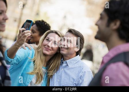 Menschen im Freien in der Stadt im Frühjahr Mal eine Frau mit ihrem Handy eine Foto A Gruppe von Freunden Männernund - Stockfoto