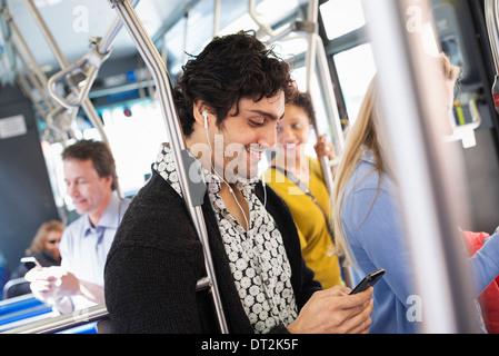 New York City Park Menschen Männer und Frauen auf einem Stadtbus ÖPNV in Kontakt zu bleiben, einen jungen Mann sein - Stockfoto