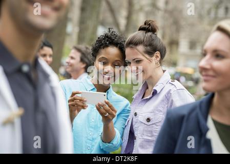 Menschen im Freien in der Stadt Frühling Zeit New York City Park zwei Frauen in einer Gruppe von Freunden mit Blick - Stockfoto