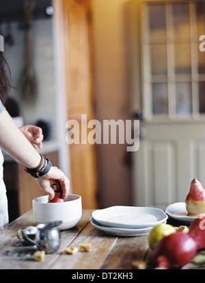 Eine Frau in einer Küche kochen Dipping frische Bio-Birnen in einer Sauce zum Nachtisch frische Zutaten brauner - Stockfoto